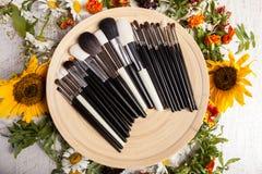Tipo differente di spazzole Make up su un piatto accanto al fiore selvaggio Immagini Stock