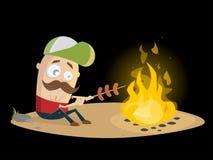 Tipo divertente che griglia le salsiccie al fuoco di accampamento Immagine Stock Libera da Diritti
