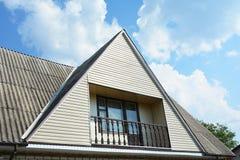 Tipo do frontão e do vale de construção do telhado com balcão acolhedor Construção da casa do sótão da construção com tipos difer Fotos de Stock