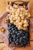 Tipo dois de uvas maduras frescas azuis e verdes em um vintage tr velho Imagem de Stock Royalty Free