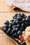 Tipo dois de uvas maduras frescas azuis e verdes em um vintage tr velho Fotos de Stock Royalty Free