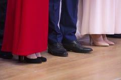 Tipo dos pés das mulheres em sapatas à moda e em vestidos de bola bonitos no fundo foto de stock royalty free