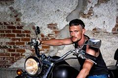 Tipo duro com sua bicicleta na frente de uma parede de tijolo Foto de Stock