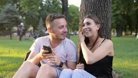 Tipo e ragazza che ascoltano la musica sul telefono in un parco sotto un albero archivi video