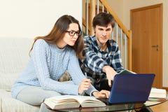 Tipo e ragazza che preparano per l'esame con il computer portatile Immagine Stock Libera da Diritti