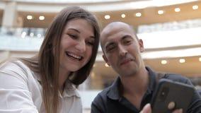 Tipo e ragazza che si siedono nel centro commerciale sui precedenti della fontana che discute le foto sul telefono e sulla risata archivi video