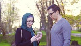 Tipo e ragazza nel hijab che parlano sulla via nel parco video d archivio