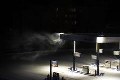 Tipo em uma estação de gasolina abandonada no inverno na noite, tempestade de neve imagem de stock royalty free
