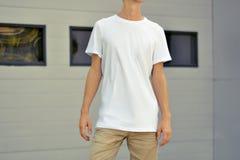 Tipo esile di Yong in un supporto in bianco della maglietta vicino al prof. del metallo bianco immagini stock libere da diritti