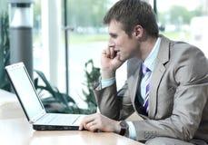 Tipo europeo attraente che parla sul telefono mentre per mezzo del computer portatile fotografia stock libera da diritti