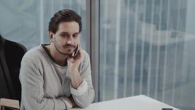 Tipo europeo attraente che parla sul telefono mentre per mezzo dello smartphone nel luogo di lavoro stock footage