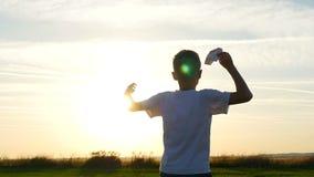 Tipo felice che gioca con un aeroplano di carta in un campo al sole Siluetta al tramonto stock footage