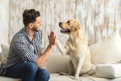 Tipo felice che si siede su un sofà e che esamina cane Fotografie Stock Libere da Diritti