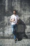 Tipo felice che sta al sole con la bevanda fotografia stock libera da diritti