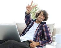 Tipo felice con un computer portatile che mostra un gesto di conquista Concetto di successo Immagini Stock