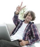 Tipo felice con un computer portatile che mostra un gesto di conquista Concetto di successo Fotografia Stock