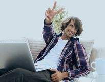 Tipo felice con un computer portatile che mostra un gesto di conquista Concetto di successo Fotografie Stock