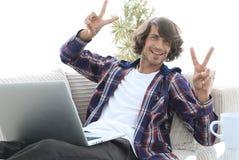 Tipo felice con un computer portatile che mostra un gesto di conquista Concetto di successo Fotografia Stock Libera da Diritti