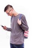 Tipo felice dei pantaloni a vita bassa con lo zaino e per mezzo di uno Smart Phone ascoltare musica con le cuffie Fotografia Stock Libera da Diritti