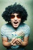 Tipo feliz loco en peluca afro con las porciones de dinero Imágenes de archivo libres de regalías