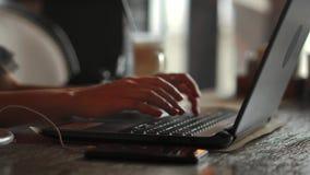 tipo femenino de las manos 4k en el teclado del ordenador portátil que toca el panel táctil con el teléfono elegante de los finge almacen de metraje de vídeo