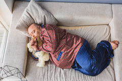 Tipo grasso che dorme sul sofà immagine stock