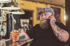 Tipo grasso che spende tempo in pub mentre bevendo birra inglese fotografie stock libere da diritti