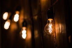 Tipo incandescente bulbos de Edison del vintage en la pared de madera Foto de archivo libre de regalías