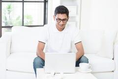 Tipo indiano che per mezzo del computer a casa Fotografia Stock Libera da Diritti