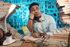 Tipo indiano etnico della corsa mista circondato dai libri in biblioteca Lo studente sta sembrando annoiato Fotografie Stock Libere da Diritti