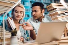 Tipo indiano etnico della corsa mista e ragazza bianca circondati dai libri in biblioteca Gli studenti stanno esaminando le note Immagini Stock Libere da Diritti