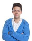 Tipo ispanico sorridente in una maglia con cappuccio blu Immagine Stock