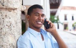 Tipo latino con il telefono in una città coloniale che ride della macchina fotografica Immagine Stock