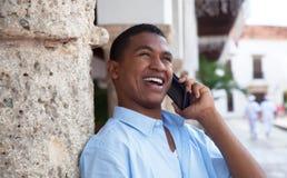 Tipo latino felice con il telefono in una città coloniale Immagini Stock Libere da Diritti