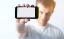 Tipo in maglietta bianca che tiene uno Smart Phone in sua mano su un briciolo Fotografie Stock