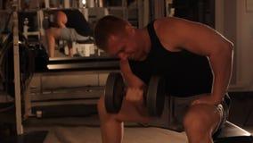 Tipo muscolare del culturista che fa gli esercizi con le teste di legno in palestra archivi video