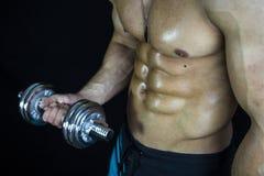Tipo muscolare del culturista che fa gli esercizi con le teste di legno sopra fondo nero Fotografie Stock Libere da Diritti