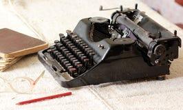 Tipo negro escritor del metal del vintage al lado de una pila de cuadernos viejos, de pares de lentes y de un lápiz en un mantel  fotos de archivo