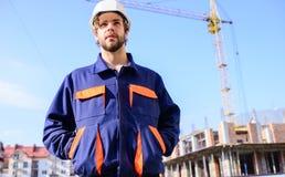 Tipo nel supporto protettivo del casco davanti a costruzione ed alla gru Controlli il processo della costruzione Costruttore in v fotografie stock