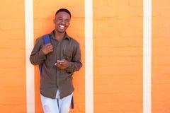Tipo nero felice che ride con il telefono cellulare contro la parete arancio Immagine Stock Libera da Diritti