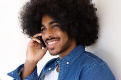 Tipo nero felice che usando pone mobile Fotografia Stock