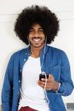 Tipo nero sorridente che ascolta la musica sullo Smart Phone Immagini Stock Libere da Diritti