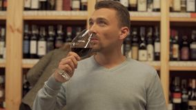 Tipo pensieroso bello con un vetro di vino in un negozio di alcolici La donna nei precedenti sta scegliendo una bottiglia di vino archivi video