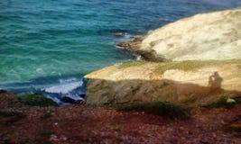 Tipo que toma una imagen de la costa, colocándose en el borde de un acantilado Imagenes de archivo