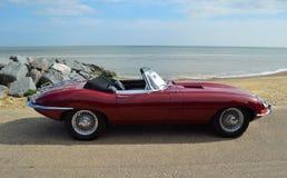 Tipo rojo clásico coche convertible de Jaguar E de motor parqueado en la 'promenade' de la orilla del mar fotos de archivo