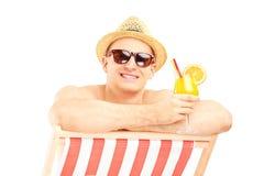 Tipo senza camicia sorridente con il cocktail che posa su una sedia di spiaggia Immagini Stock