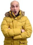 Tipo sorprendido que lleva una chaqueta amarilla del invierno Imagen de archivo libre de regalías