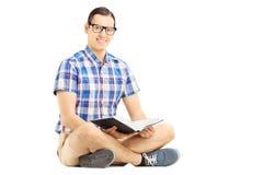 Tipo sorridente con i vetri che si siedono su un pavimento e sulla lettura del libro fotografia stock