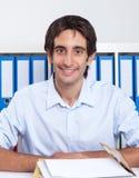 Tipo spagnolo che lavora allo scrittorio Fotografia Stock