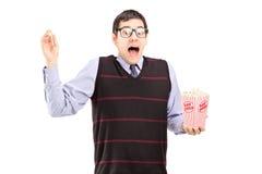 Tipo spaventato che tiene un contenitore di popcorn e che grida Fotografia Stock Libera da Diritti